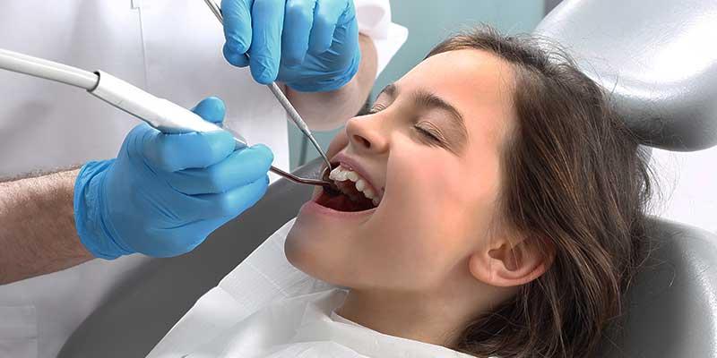 children's dentist cleaning little girl's teeth