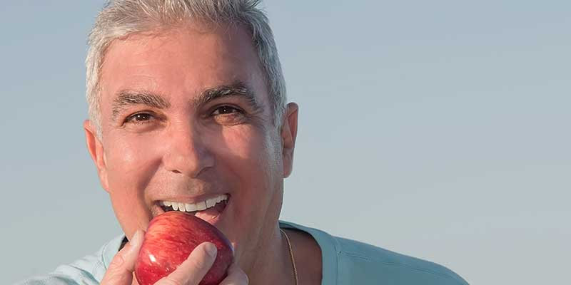 man with dental implant eating an apple